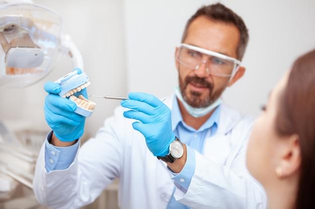 Dentista maschio maturo con esperienza che spiega igiene dentale al suo paziente femminile, tenente muffa dei denti