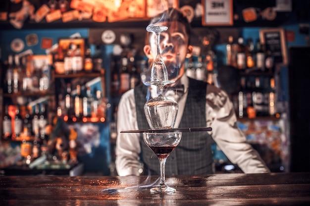 Il barman esperto fa un cocktail stando in piedi vicino al bancone del bar in discoteca