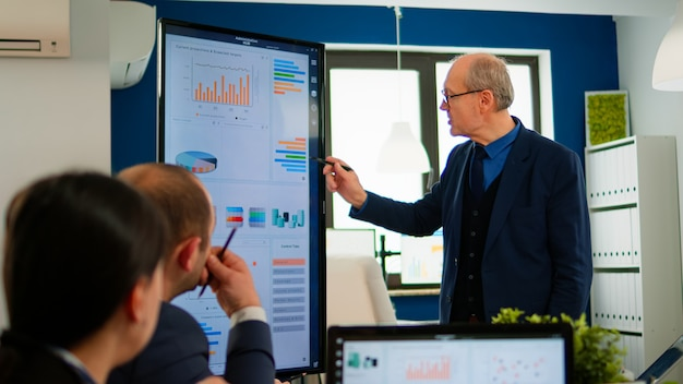 Capo progetto esperto che analizza la presentazione finanziaria durante la conferenza d'affari nella sala di brainstorming utilizzando dispositivi digitali. team multietnico che lavora in una società di avvio professionale durante me