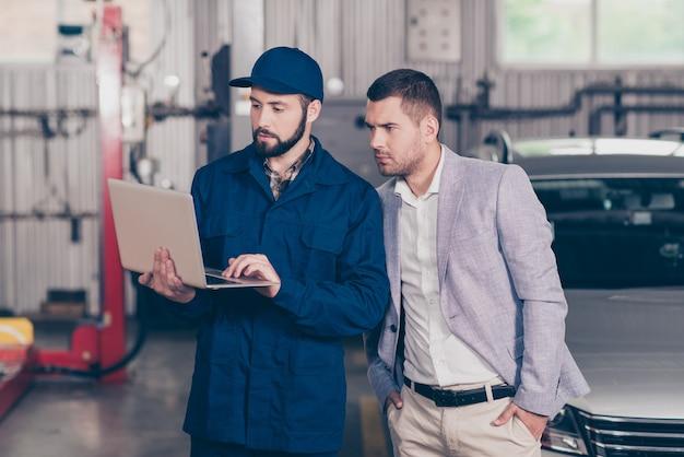 Lo specialista esperto nel laptop della tenuta del cappuccio mostra le informazioni del cliente