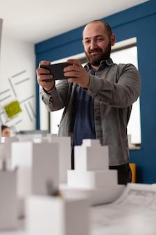 Architetto esperto che guarda lo smartphone sul posto di lavoro