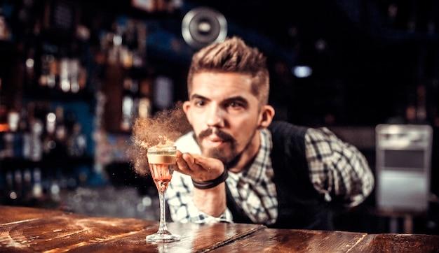 Il bartending esperto pone gli ultimi ritocchi su un drink stando in piedi vicino al bancone del bar