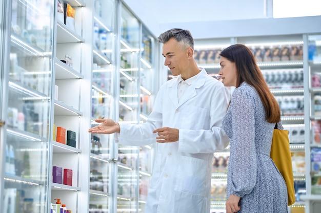 Farmacista esperto consulente in veste bianca che consiglia nuovi prodotti sanitari a una cliente femminile