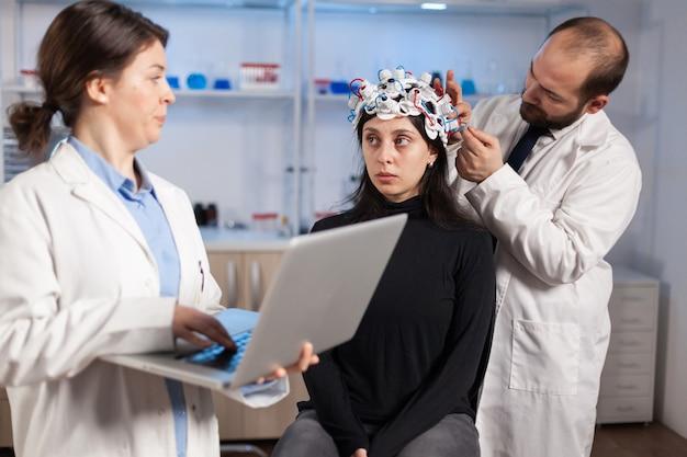 Medico esperto in neuroscienze che sviluppa esperimenti sul cervello con laptop che spiega agli effetti collaterali della donna del trattamento del sistema nervoso. team di scienziati che lavorano nel laboratorio di ricerca neurologica.