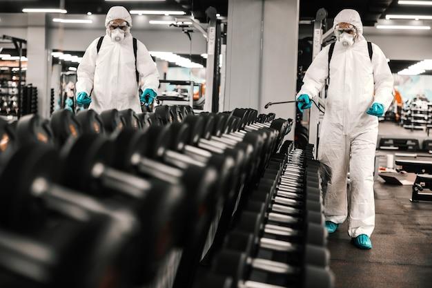 Esperto in abbigliamento protettivo pulisce manubri e attrezzature per l'allenamento. concetto di coronavirus, prevenzione covid19, situazione pandemica. antisettico, disinfezione, pulizia, assistenza sanitaria, antibatterico