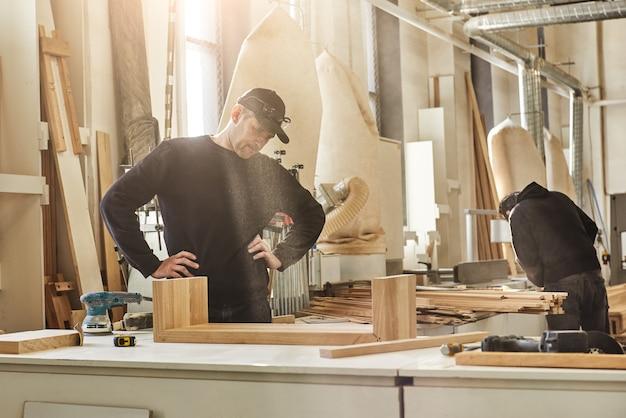 Esperto creatore di segatura ritratto di un lavoratore che fa il suo lavoro con il legno utilizzando la rettificatrice