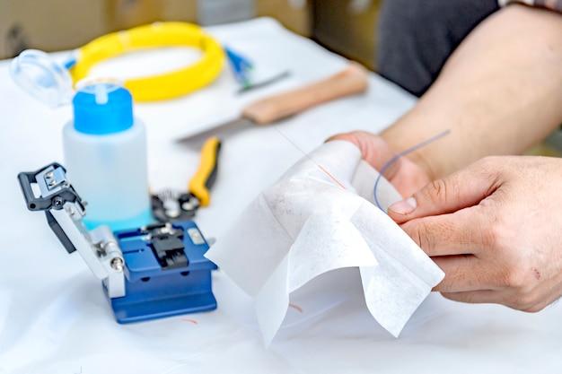 Tecnico esperto pulizia di cavi in fibra ottica con detergente