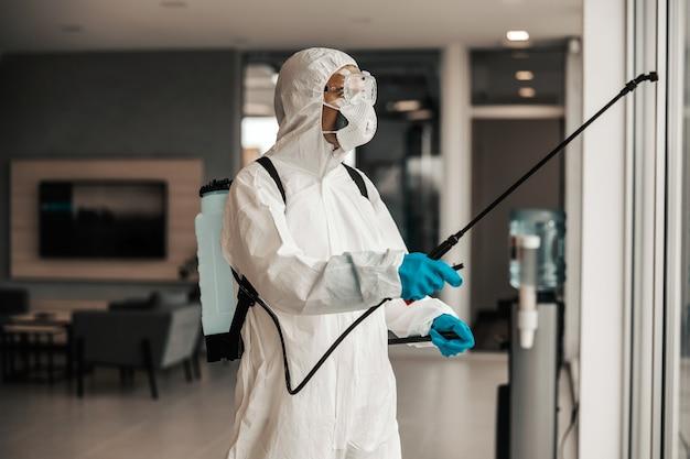 Esperto in divisa protettiva bianca con mascherina e occhiali disinfezione spazio e finestra
