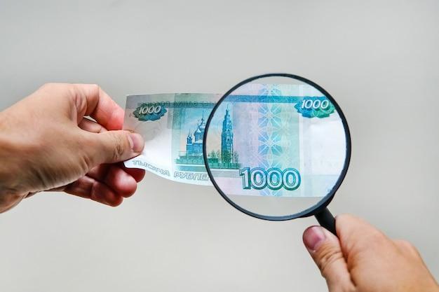 L'esperto con la lente d'ingrandimento controlla i soldi sospetti cerca filigrane su carta delle banconote false. lente d'ingrandimento, lente d'ingrandimento, lente d'ingrandimento, lenti d'ingrandimento, lente d'ingrandimento