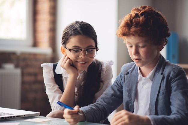 Spiegazione della lezione. ragazza dai capelli scuri che spiega lezione al suo compagno di classe