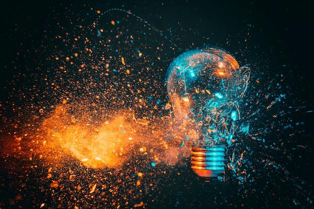 Esplosione di una lampadina a filamento. parete nera e toni blu e arancioni.