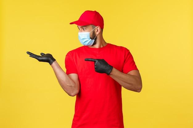Consegna espressa durante la pandemia, covid-19, spedizione sicura, concetto di shopping online. corriere felice eccitato in uniforme rossa e maschera medica, guanti, dito puntato e guardando il palmo con il prodotto