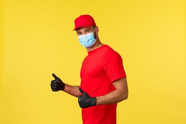 Consegna espressa durante la pandemia, covid-19, spedizione sicura, concetto di shopping online. bel corriere sorridente in uniforme rossa, maschera medica e guanti dpi, pollice in su garantisce una spedizione sicura e veloce.