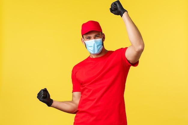 Consegna espressa durante la pandemia, covid-19, spedizione sicura, concetto di shopping online. felice corriere gioioso con berretto e maglietta uniforme rossa, pompa a pugno che canta grandi buone notizie, indossa una maschera medica