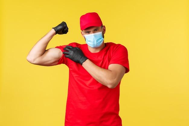 Consegna espressa durante la pandemia, covid-19, spedizione sicura, concetto di shopping online. corriere forte in uniforme rossa, maschera e guanti medici, bicipiti flessibili, muscoli forti in mostra