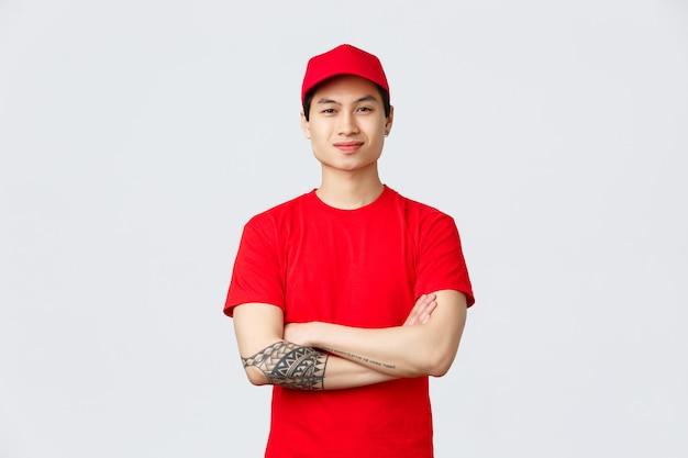 Consegna espressa, spedizione e concetto di logistica. fiducioso uomo asiatico che lavora in una compagnia di consegne, indossa un'uniforme rossa con berretto e maglietta, braccia incrociate sul petto e sorridente.