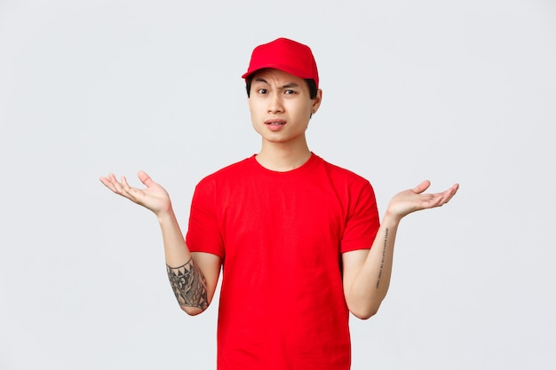 Consegna espressa, spedizione e concetto di logistica. il corriere non capisce perché, indossa berretto e maglietta rossi, alza le spalle con le mani aperte di lato, fa una smorfia seccata, si lamenta