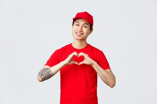 Consegna espressa, spedizione e concetto di logistica. corriere asiatico bello e amichevole in berretto rosso e maglietta, uniforme aziendale, mostra il gesto del cuore e sorride felice, si prende cura di clienti e clienti