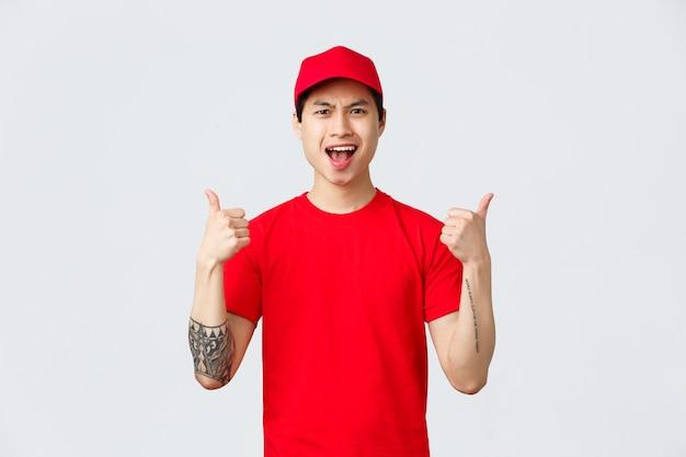 Consegna espressa, spedizione e concetto di logistica. corriere asiatico allegro e bello in maglietta e berretto rossi, mostra il pollice in su, incoraggia a continuare a lavorare, essere il migliore, cantare in festa