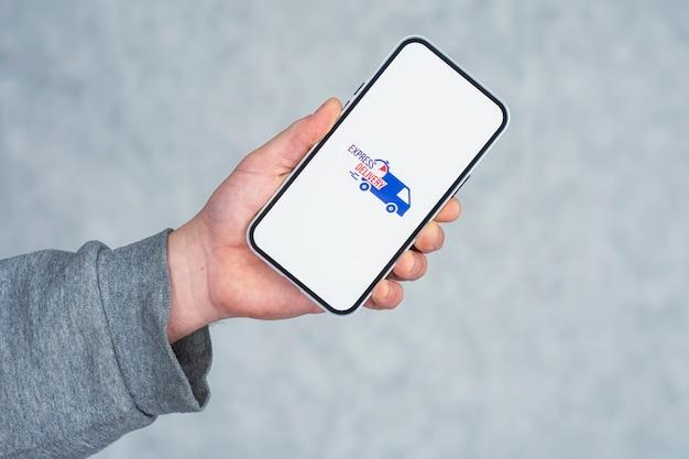 Consegna espressa nel tuo telefono. un uomo tiene in mano uno smartphone con un'icona su uno schermo bianco.