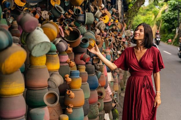 Esprimi positività. bella donna internazionale che mantiene il sorriso sul viso mentre sceglie vasi di argilla per il regalo