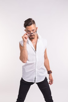 Concetto di espressione e persone - giovane uomo bello che ti guarda attraverso gli occhiali su bianco