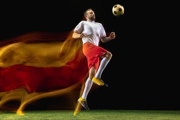 Espressione. giovane calciatore maschio caucasico o calciatore in abbigliamento sportivo e stivali che calcia la palla per l'obiettivo in luce mista sulla parete scura. concetto di stile di vita sano, sport professionistico, hobby.
