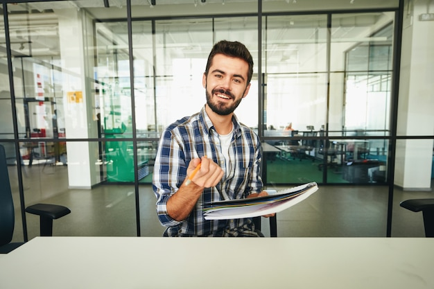 Uomo castana espressivo che indica matita alla macchina fotografica e che sorride