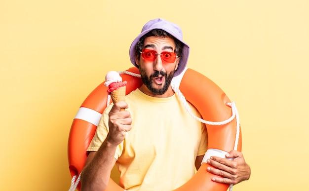 Uomo barbuto pazzo espressivo che indossa cappello e occhiali da sole con un gelato