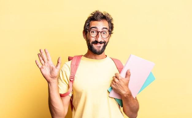 Uomo pazzo espressivo che sorride felicemente, agitando la mano, accogliendoti e salutandoti. concetto di studente adulto