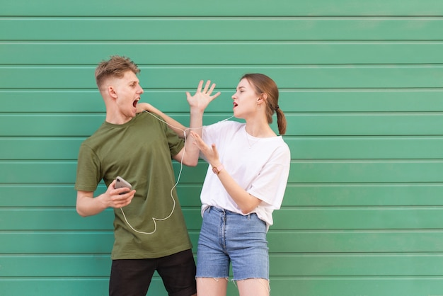 Il giovane espressivo e la ragazza ascoltano la musica in cuffia su un verde