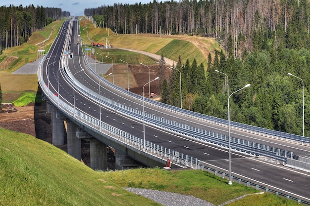 La superstrada attraversa la foresta, il ponte a traliccio in acciaio è sostenuto da supporti in cemento armato.