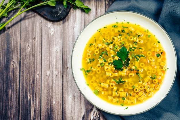 Squisita zuppa di pollo e verdure con piccoli noodles e prezzemolo fatta in casa spazio per copia vista dall'alto