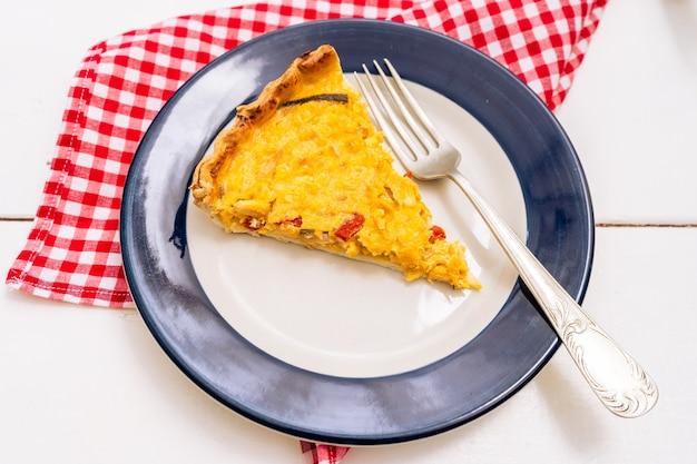 Squisita porzione di torta di mais fatta in casa o quiche con cipolla, peperone rosso ed erba cipollina su un piatto bianco con un bordo blu. cibo sano e naturale.