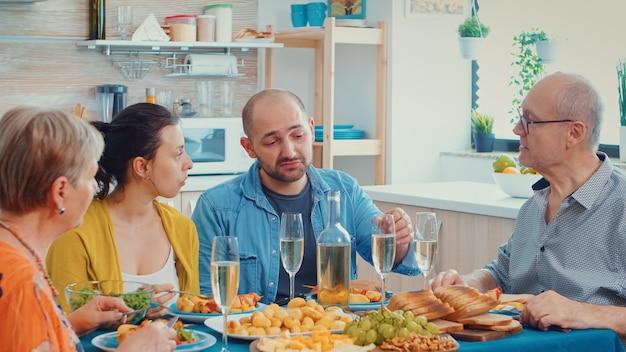 Famiglia allargata che interagisce mentre si mangia al tavolo da pranzo in cucina. multi generazione, quattro persone, due coppie felici che parlano e mangiano durante una cena gourmet, godendosi il tempo a casa.