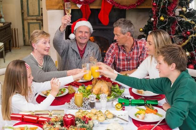 Famiglia estesa che tosta alla cena di natale