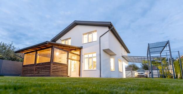 Vista esterna della moderna casa bianca con cortile, patio, prato verde, giardino e un'auto la sera