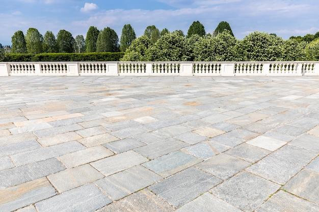 Esterno con pavimento grigio antico in pietra. pavimentazione strutturata dell'annata e cielo blu nei precedenti.
