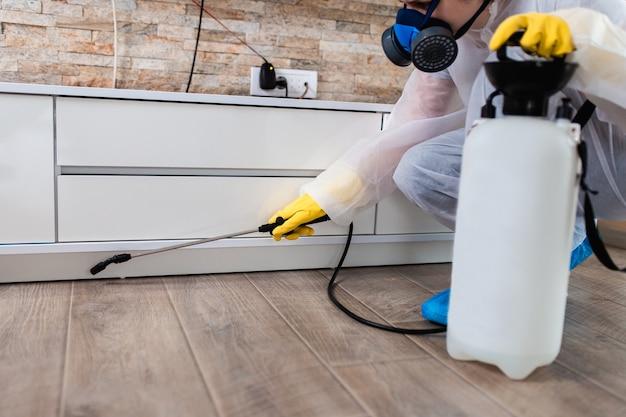 Sterminatore in abbigliamento da lavoro che spruzza pesticidi con spruzzatore.