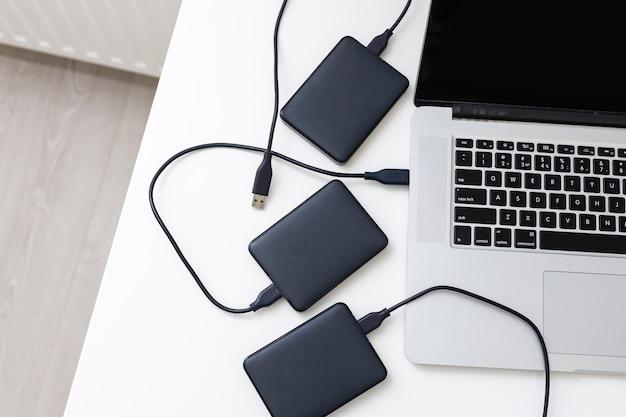 Disco rigido esterno di backup collegato al laptop. foto di alta qualità