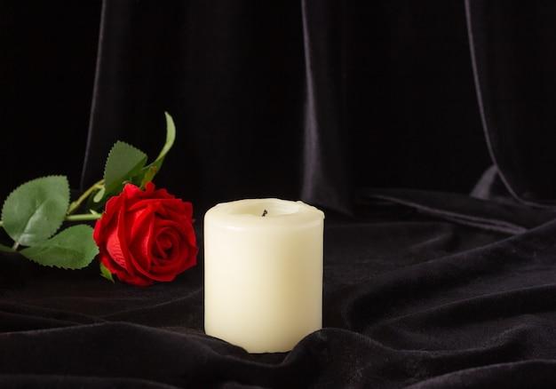 Una candela spenta e una rosa rossa su sfondo nero