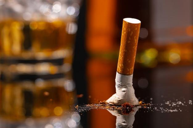 Estinto mozzicone di sigaretta sulla tavola nera vicino foto