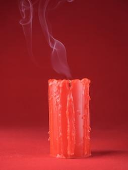 Una candela rossa spenta con fumo con macchie su uno sfondo rosso. copia spazio.