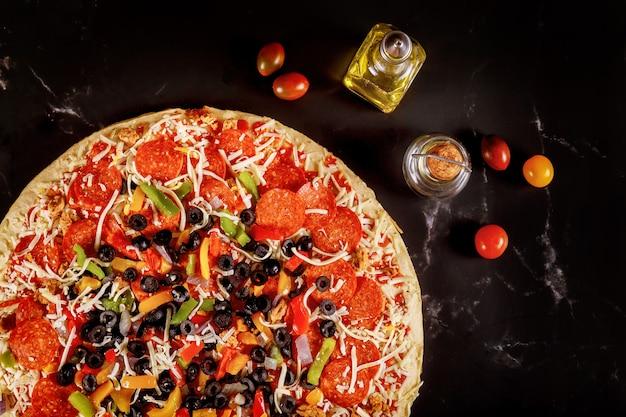 Pizza extra large con olive, peperoni e pomodori su fondo nero.