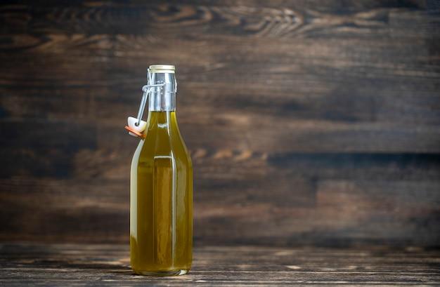 Olio extra vergine di oliva in bottiglia di vetro rustica su fondo di legno, primo piano, spazio di copia