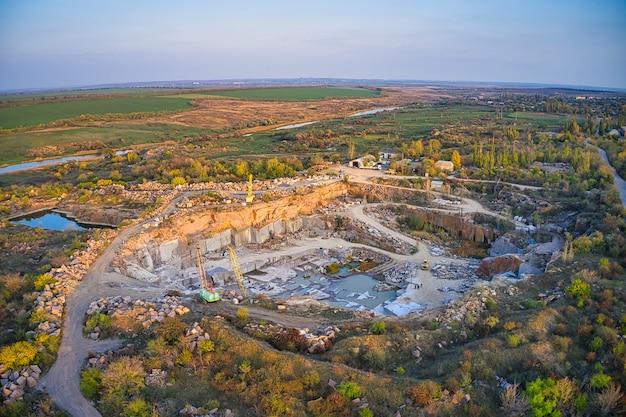 Estrazione di minerali con l'aiuto di attrezzature speciali vicino a un piccolo lago nella calda luce della sera nella pittoresca ucraina. ripresa aerea panoramica con drone