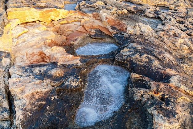 Estrazione del sale marino dall'evaporazione dell'acqua di mare in piscine di pietra. stagni di sale al largo della costa di gozo e malta.