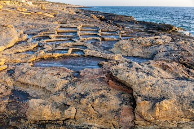 Estrazione del sale marino dall'evaporazione dell'acqua di mare in piscine di pietra.