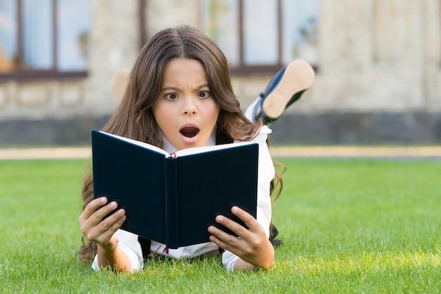Lettura extracurricolare. libro di lettura sveglio del bambino piccolo all'aperto. educazione di base. la bambina adorabile impara a leggere. lo studio del concetto. uniforme scolastica della scolara che pone sul prato inglese con il libro preferito.