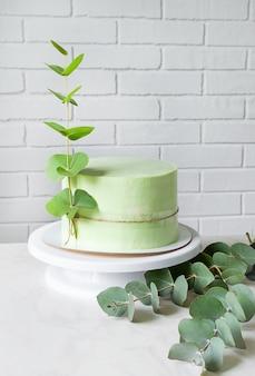 Straordinaria torta verde festiva decorata con un rametto di eucalipto. copia spazio.